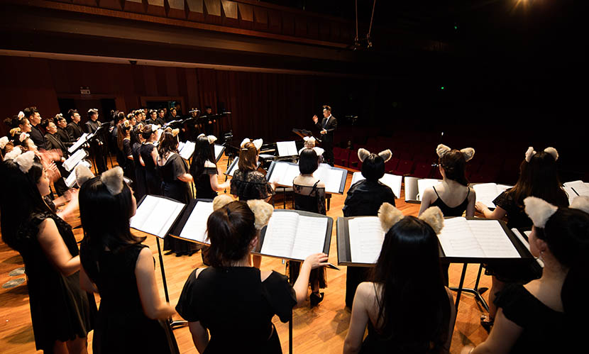 Members of the Rainbow Chamber Choir rehearse in a concert hall. Courtesy of Rainbow Chamber Choir