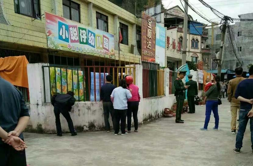People try to look into the kindergarten where a man assaulted 12 children with a kitchen knife, Pingxiang, Guangxi Zhuang Autonomous Region, Jan. 4, 2017. From Weibo
