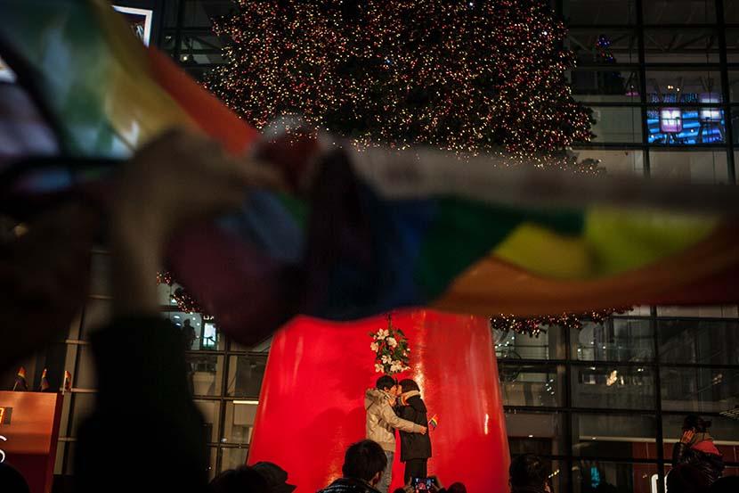 A lesbian couple kiss each other during an event in Shanghai, Dec. 22, 2013. Sun Zhan/Sixth Tone