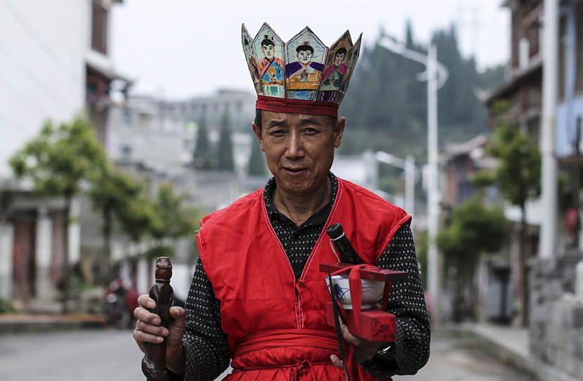 Zhang Maoqing, dressed in his Nuo opera costume, shows ceremonial objects in Shaowo Town, Guizhou province, June 14, 2016. Li Kun/Sixth Tone