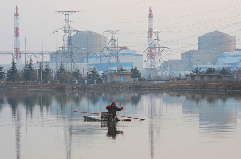 Tianwan Nuclear Power Plant is visible behind a fisherman in Lianyungang, Jiangsu province, Aug. 8, 2016. Geng Yuhe/VCG